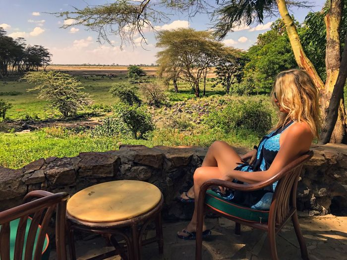 Side view of young woman sitting on chair by retaining wall at amboseli national park