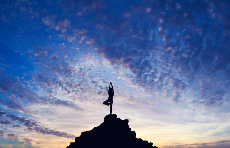 Silhouette Of Person Doing Yoga Pose On Mountain