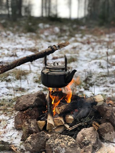 Kettle hanging over campfire in forest during winter