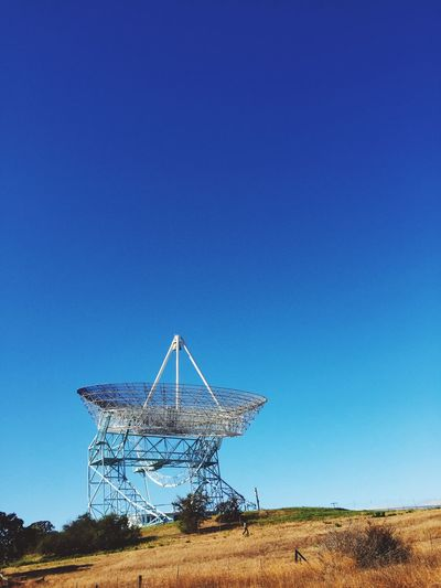 Satellite dish on field against clear blue sky