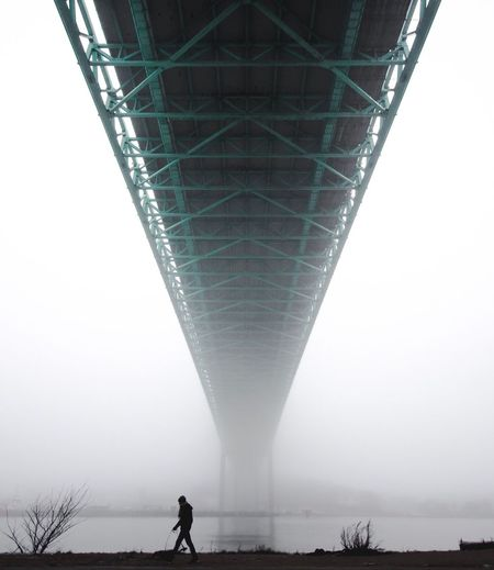 Low angle view of person walking on bridge