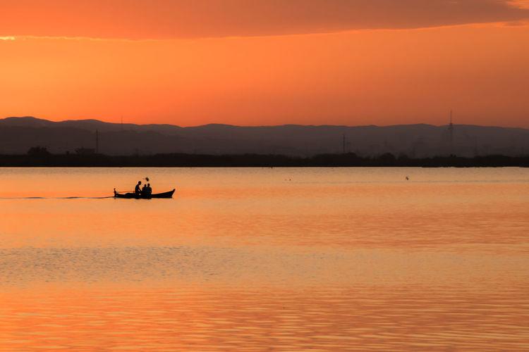 Silhouette men on boat in lake against orange sky