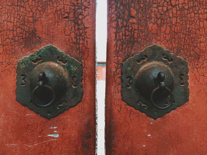 Close-up of door handles on brown door