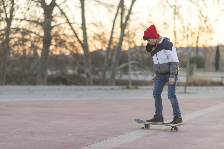 Fun Jeans Skateboarding Boys Childhood Cold Temperature Day Enjoyment Extreme Sports Full Length Leisure Activity Nature One Person Outdoors People Practicing Real People Skateboard Sport Sunset Teen Teenager Tree Warm Clothing Winter