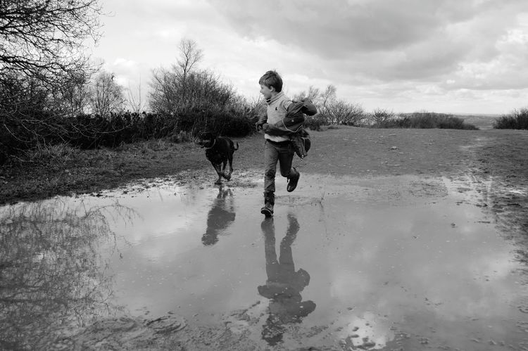 Enjoying Life Bnw_captures Black And White Black And White Photography Water Reflections Reflection_collection Kids Being Kids A Walk On The Hills Childhood Memories Jumping In Muddy Puddles Muddy Puddles Puddle A Boy And His Dog Family Showcase March