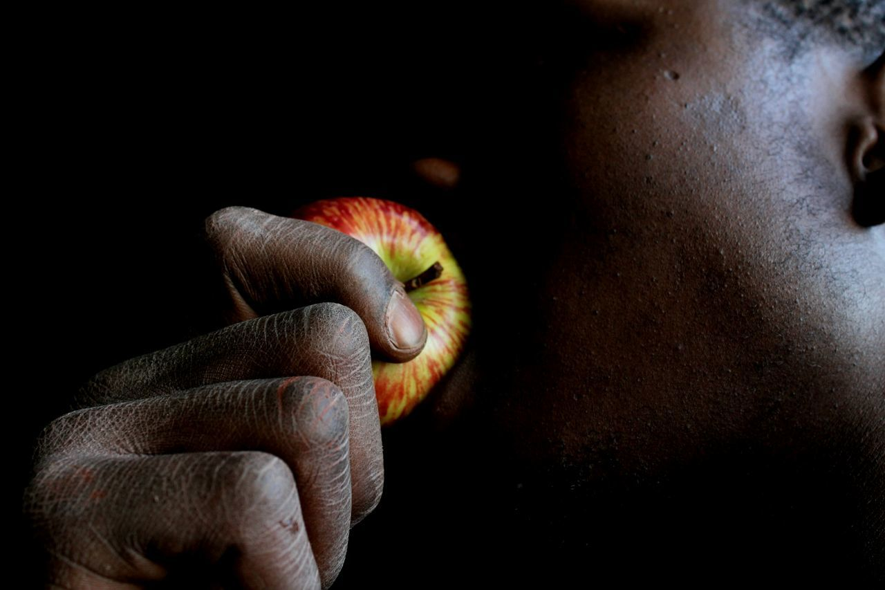 Midsection of man eating apple