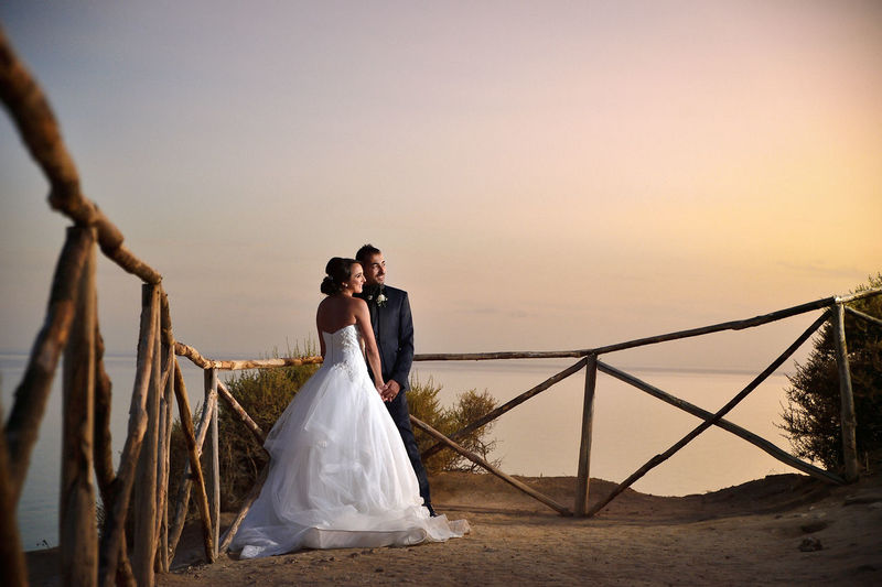 Bride And Groom Standing Against Sea During Sunset