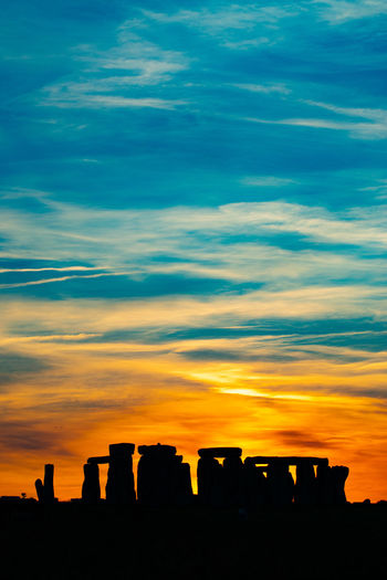 Silhouette of rocks against cloudy sky during sunset