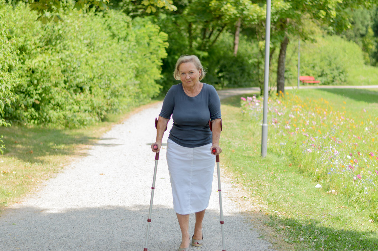 Portrait Of Senior Woman With Crutch Walking On Road By Field On Sunny Day