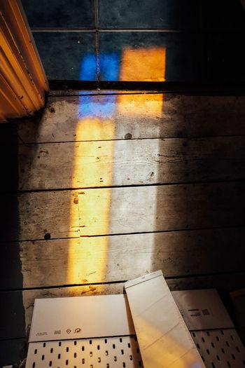 High angle view of yellow shadow on tiled floor