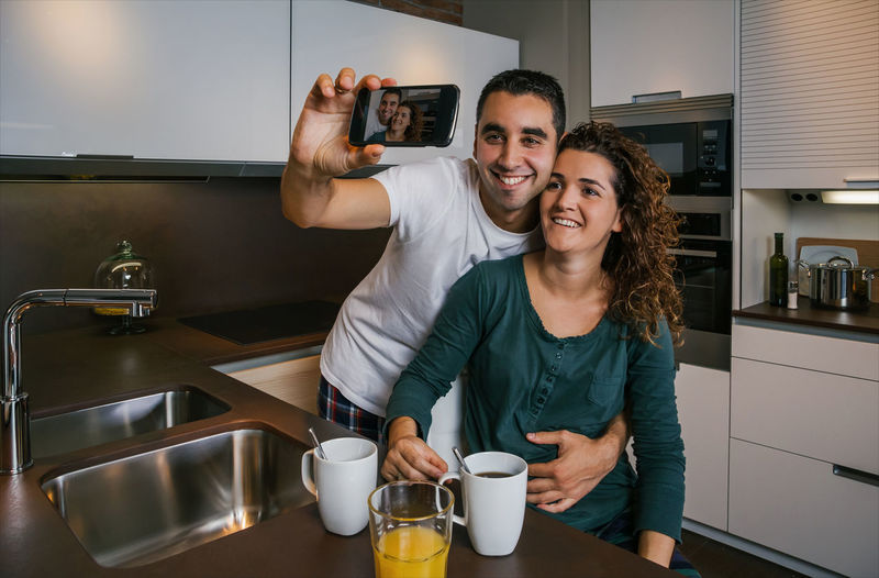 Couple having breakfast in the kitchen while taking selfie Horizontal Laughing Hug Photo Happy Phone Cell Morning Orange Juice  Coffee Indoor Real Two Young Woman Wife Smiling People Talking Taking  Married Man Male Love Looking Lifestyle Husband Cheerful Caucasian Home Girl Funny Fun Female Entertainment Mobile Together Joy Social Network Enjoying Smartphone Selfie Kitchen Breakfast Pajama Embrace Couple