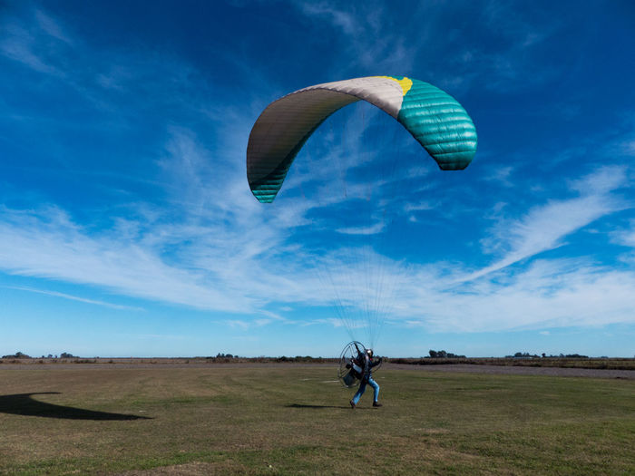 Side view of man with electric motor and parachute running on land while paragliding against sky