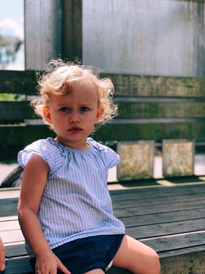 Portrait of cute boy sitting on bench