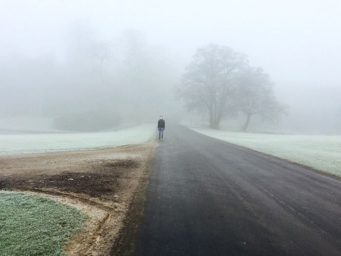 Young man standing on road in forest during foggy weather