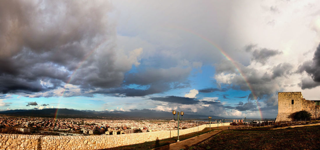 Panoramic view of rainbow over land against cloudy sky