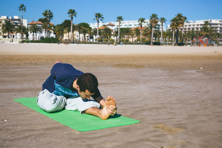 Man Stretching On Beach