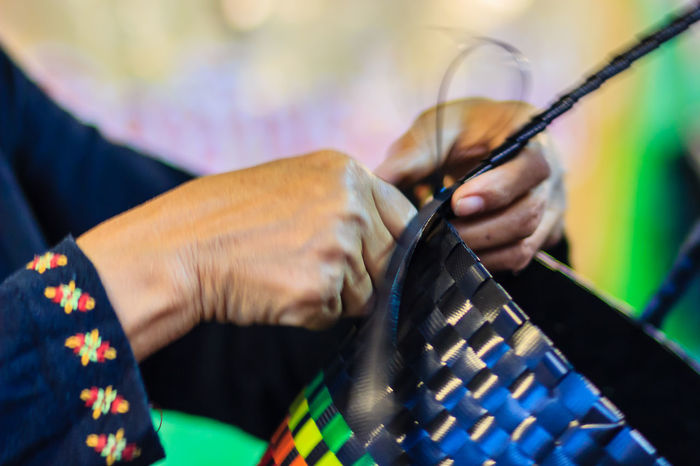 Close up hand of weaver during weaving basket made from plastic fiber. Weaver is weaving plastic basket show to the tourist in Bangkok, Thailand. Market Market Vendor Plastic Bag Weave Weaves Basket Basket Weave Close-up Day Holding Human Body Part Human Hand Indoors  Lifestyles Marketplace Men One Person People Plastic Plastic Baskets Real People Skill  Weaver Weaving Working
