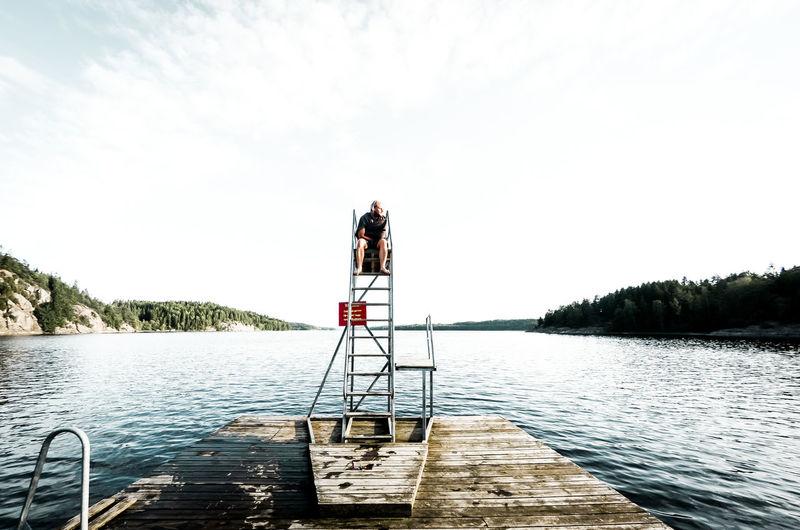 Woman sitting on diving platform by lake