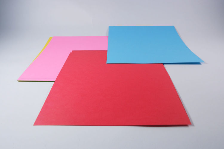 High angle view of multi colored paper against white background