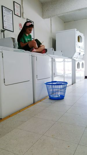 Urban Lifestyle Laundromat Passing Time Multi Tasking City Life Reading Children Children Photography Children's Portraits Learning Faces In Places Multitasking Interior Design Building Lines Composition Everyday Lives Perspective From My Point Of View Candid Photography