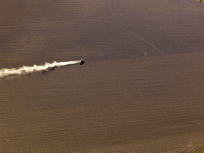 Aerial view of agriculture fields, tractor working the land.  sowing agricultural crops