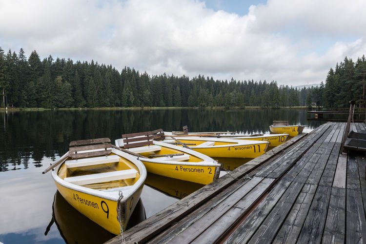 Yellow boats moored by lake against sky
