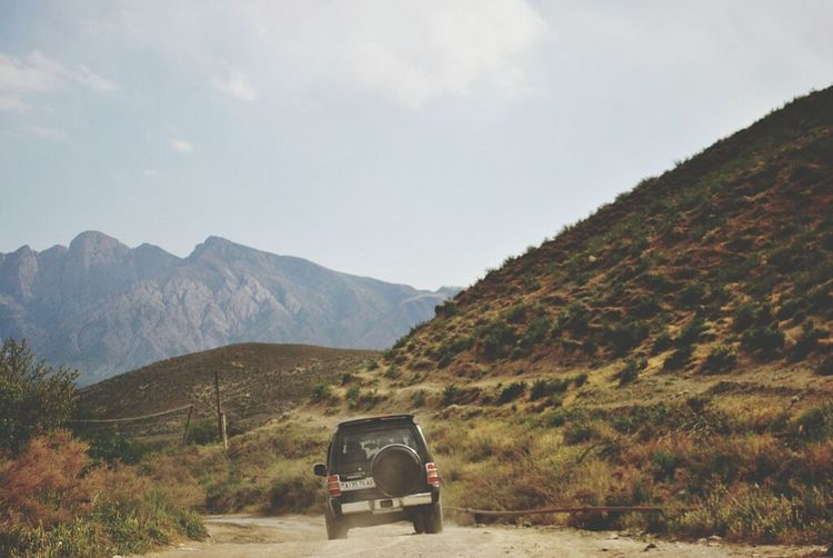Transportation Mode Of Transport Land Vehicle Landscape Mountain Car Dirt Road Sky Non-urban Scene Mountain Range Journey Plant Day Outdoors 4x4 Remote Tourism Nature Vehicle Physical Geography
