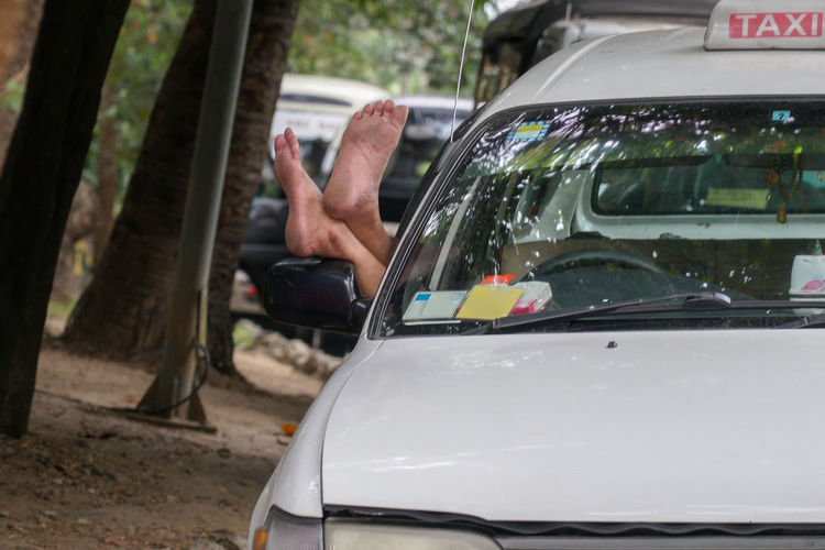 Feet of taxi driver hanging out of the car window, yangon myanmar