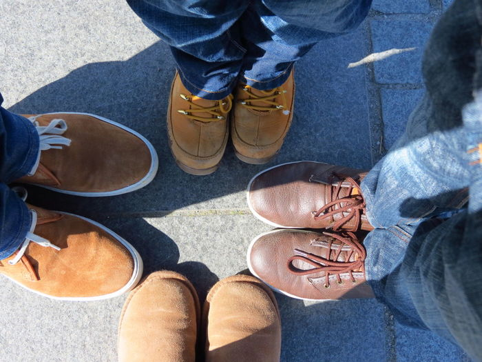 Low section of men wearing shoes standing on footpath