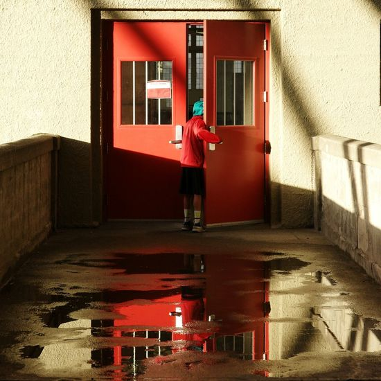 Architecture Building Exterior Mysterious Mystery Walkway Curious Curiosity Child Doorway Door Peering Through Peering Water Reflections Puddle Reflections Puddleography Puddle Red Childlike Wonder Wonder Looking In Open Door Boy Entrance Natural Light Light And Shadow The Secret Spaces