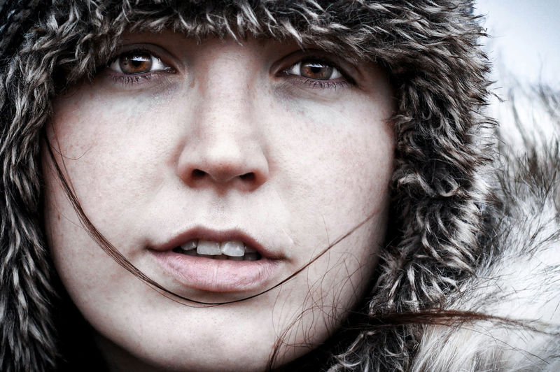 Close-Up Portrait Of Young Woman In Fur Hat