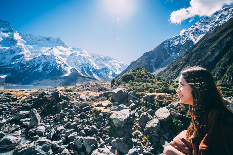 Woman on rock against sky