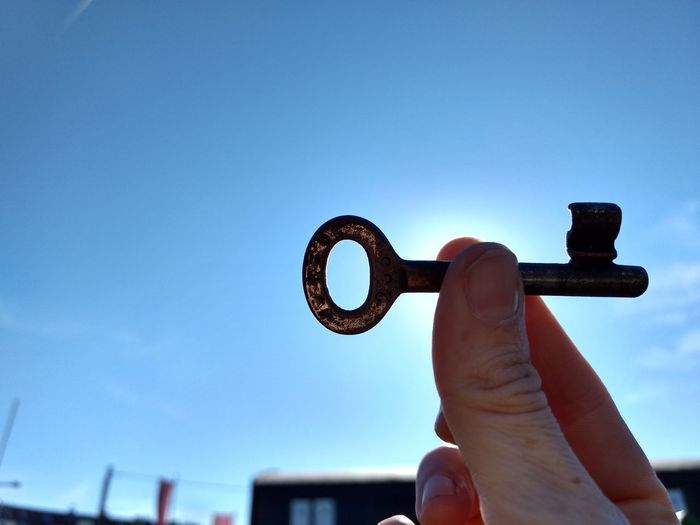 Close-up of hand holding eyeglasses against clear blue sky