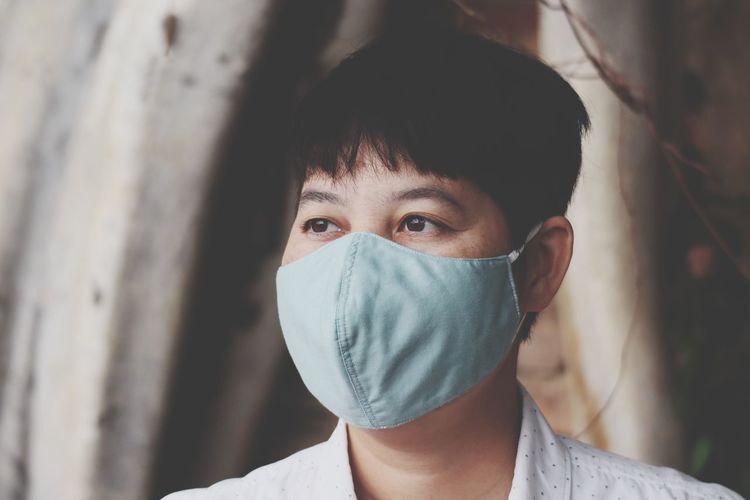 Woman wearing mask looking away while standing outdoors