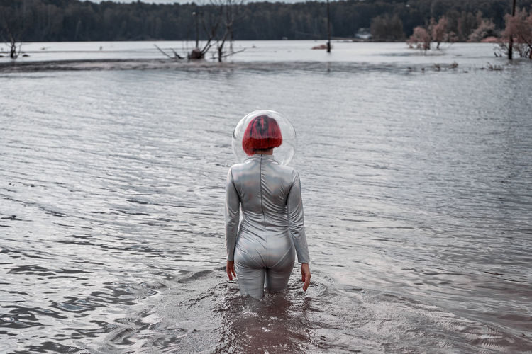 Rear view of boy standing in lake