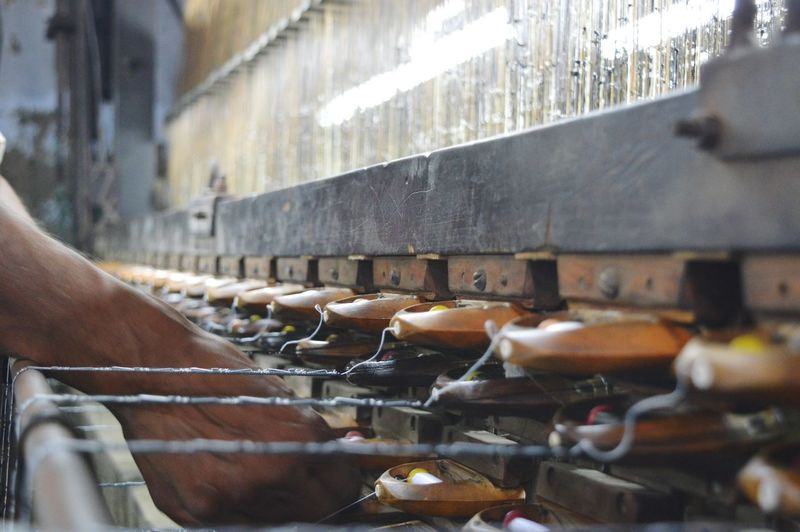 Cropped image of hand working on weaving machine