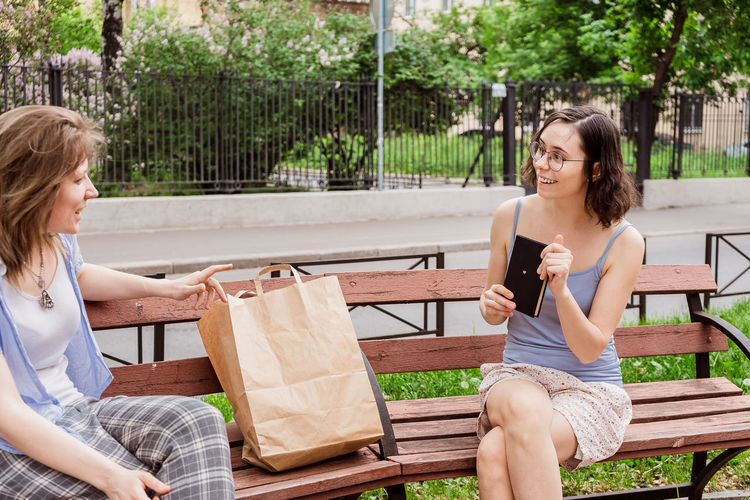 Friends are discussing a new book on the street. communication of girls with social distancing