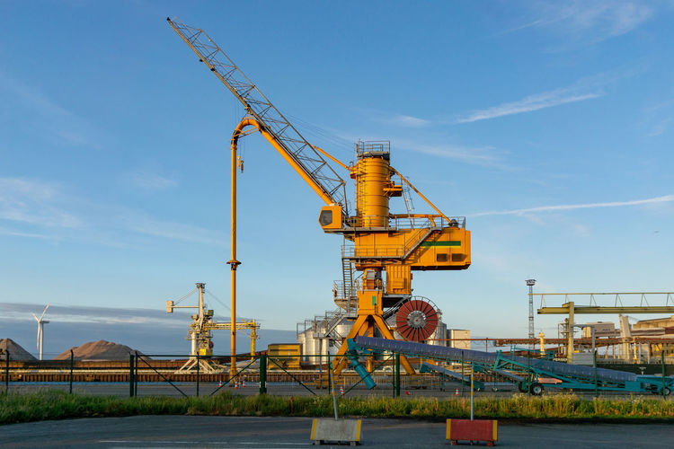 crane or loader in the harbor of rostock Industry Crane - Construction Machinery Built Structure Factory Cloud - Sky Nature Water Construction Industry Sky Machinery Architecture Construction Site Day Development Building Exterior Business Outdoors No People Metal Construction Equipment