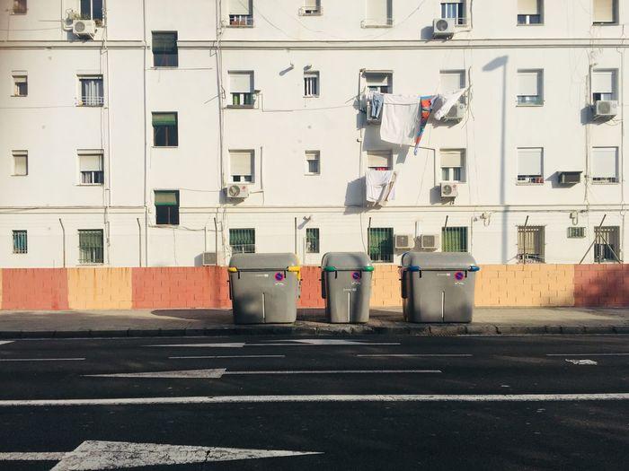 Garbage bin on street against buildings in city