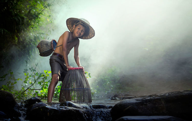 The boy enjoy fish catching in the canal at Phayao province, the northern of Thailand. Thailand Waterfall Way Of Life Rural Life Boy Catch Fish One Person Water Hat Nature Clothing Happiness Outdoors Standing Smiling