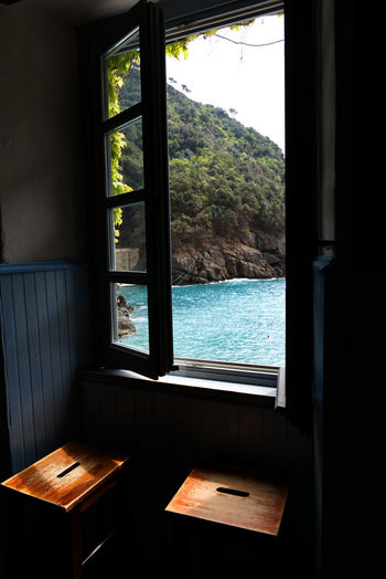 Chair and table by sea seen through window