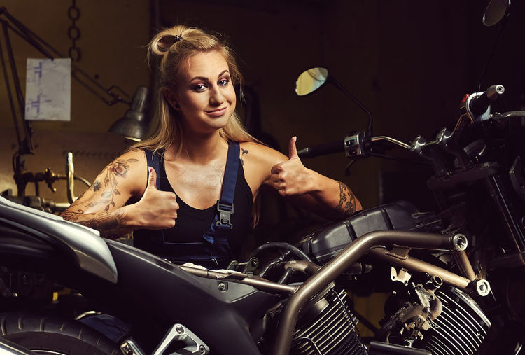 Portrait of young woman gesturing thumbs up sign with motorcycle