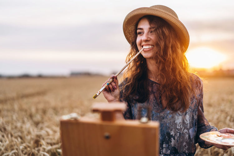 Portrait of smiling woman standing on field against sky