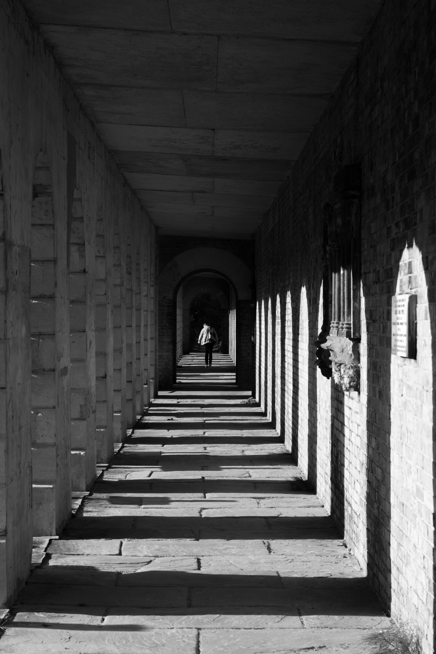 architecture, built structure, direction, the way forward, arch, day, building, arcade, one person, diminishing perspective, in a row, real people, corridor, the past, indoors, architectural column, history, rear view, lifestyles, full length, colonnade, ceiling