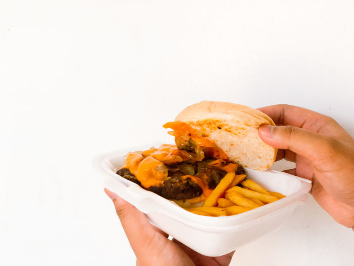 Midsection of person holding food against white background
