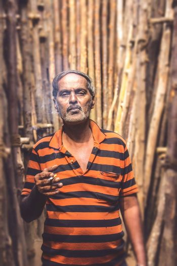 Portrait of man smoking cigarette amidst wooden structure