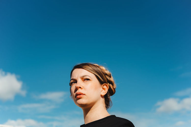 Low angle portrait of teenage girl looking away against blue sky