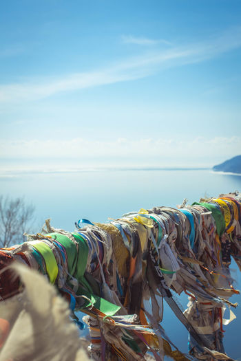 Close-up of multi colored fabrics on railing over sea against sky
