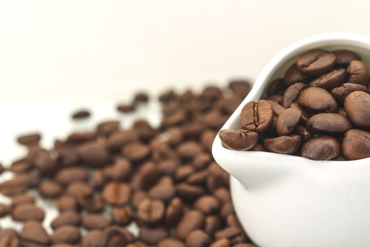 Close-up roasted coffee beans in pitcher against white background