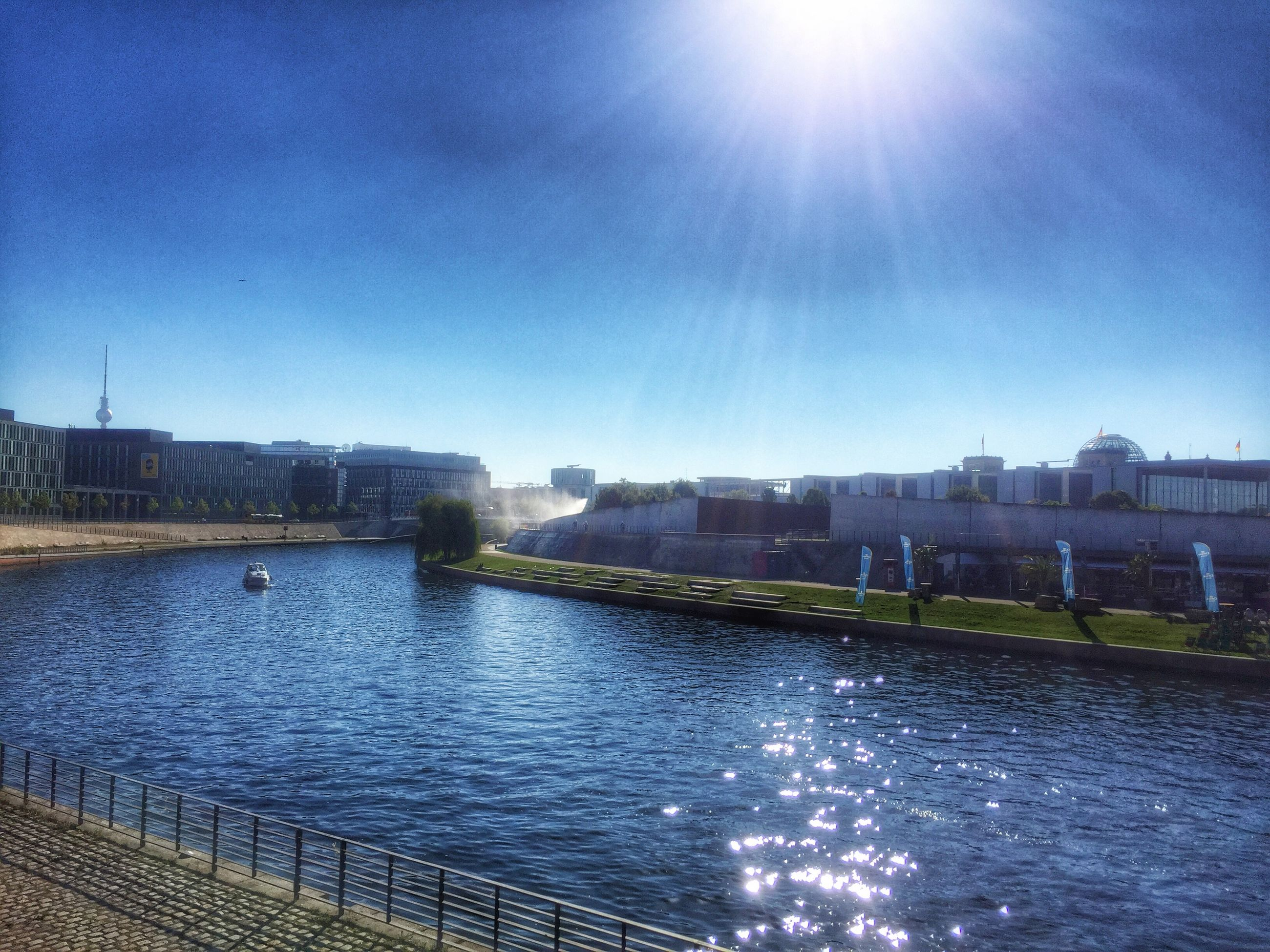 building exterior, architecture, built structure, water, sunlight, blue, city, sun, clear sky, sunbeam, river, waterfront, sunny, lens flare, sky, reflection, canal, day, rippled, outdoors